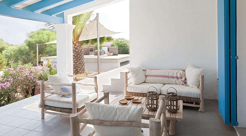 Catalina House proyecto de interiorísmo Casa Punta Prima Grau. Exterior zona sofás madera natural