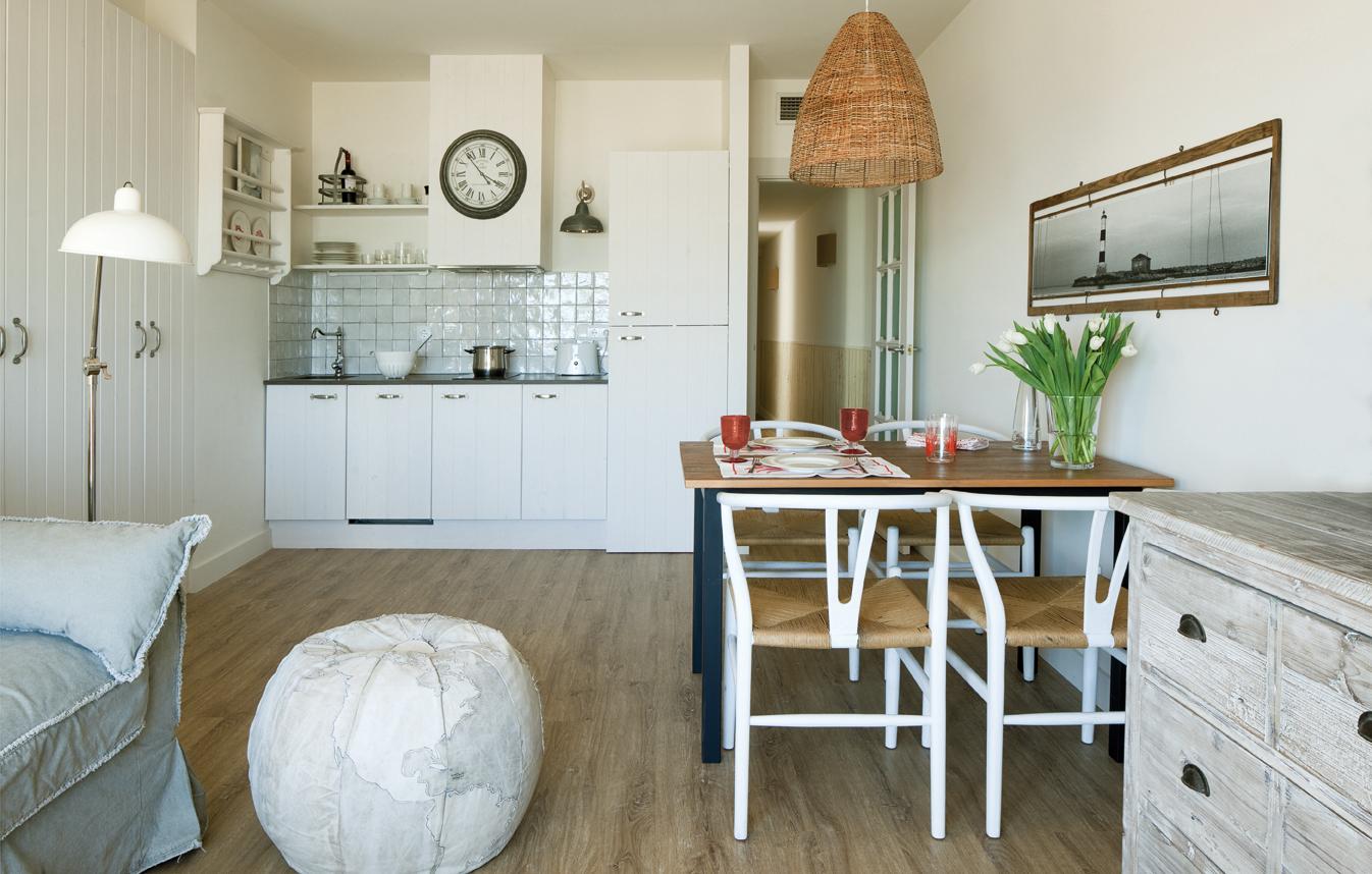 Vista general de la estancia diáfana principal que integra sala de estar, comedor y cocina.