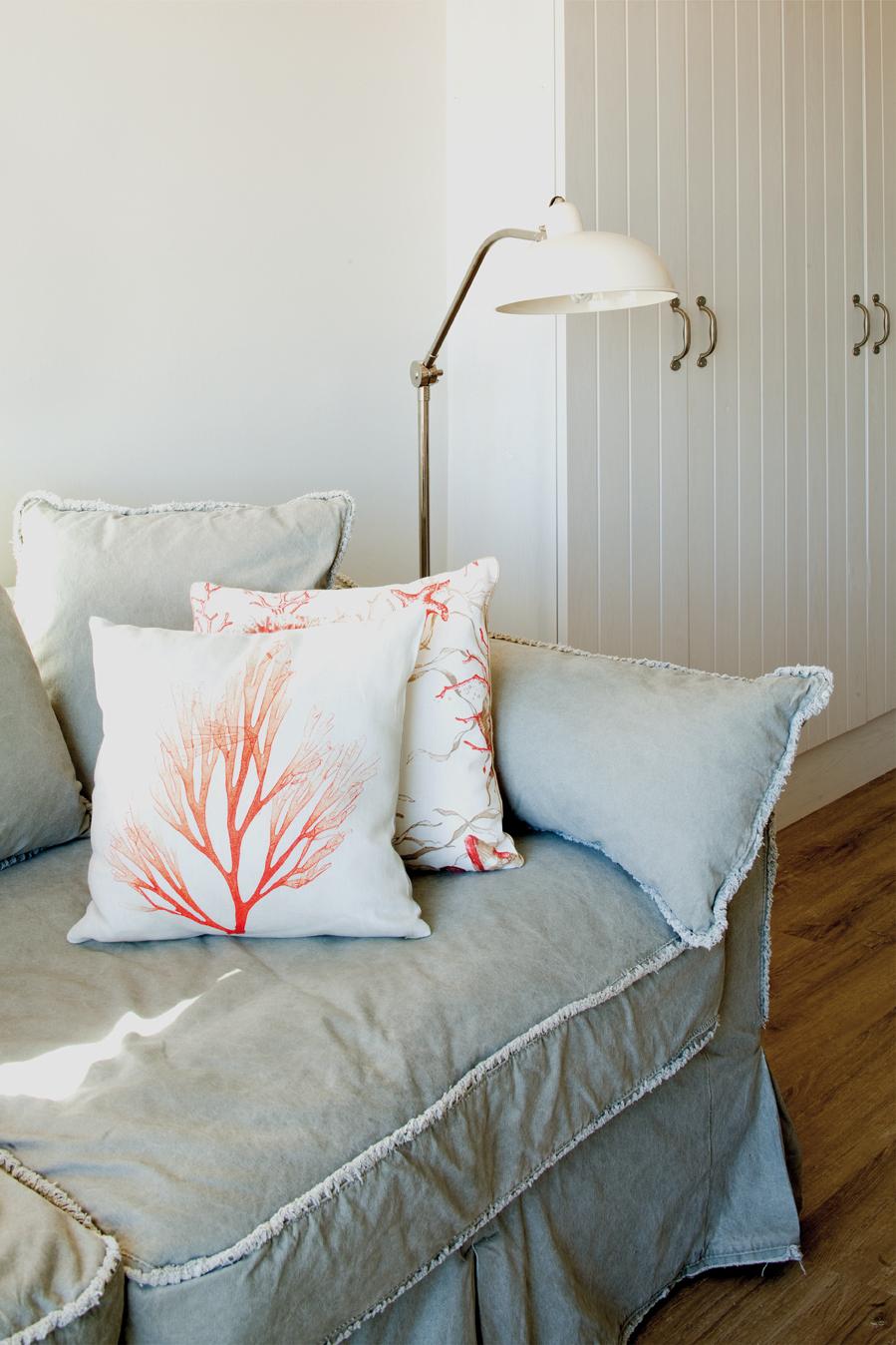 Vista de detalle del sofá con unos cojines con estampado de tonos vivos que aporta luz y color al corner