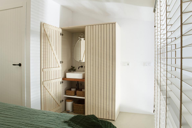 Vista de detalle del armario que esconde el lavamanos en el dormitorio.